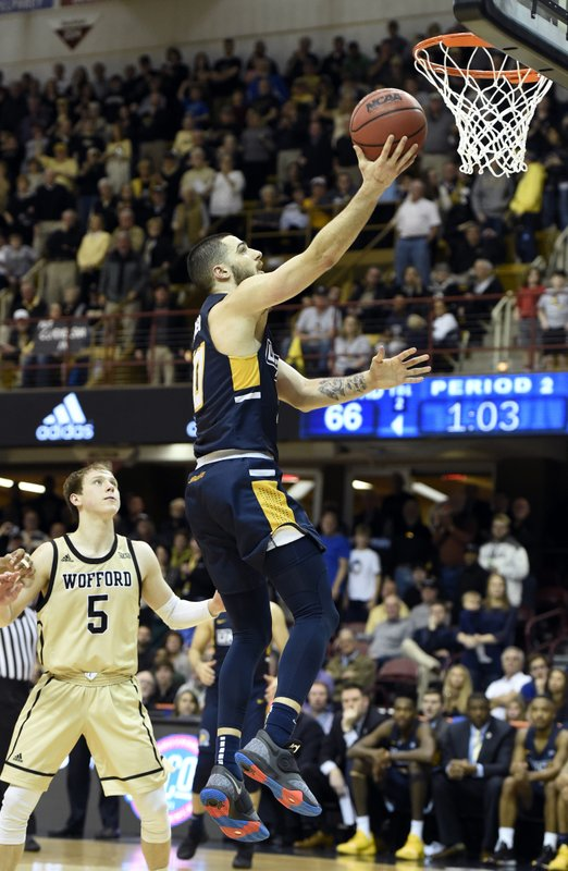 UNC-Greensboro guard Francis Alonso, right, drives the ball to the basket past Wofford guard Storm Murphy (5) in the second half of an NCAA college basketball game for the Southern Conference tournament championship, Monday, March 11, 2019, in Asheville, N. (AP Photo/Kathy Kmonicek)