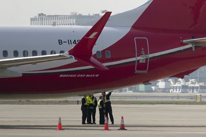 Ground crew chat near a Boeing 737 MAX 8 plane operated by Shanghai Airlines parked on tarmac at Hongqiao airport in Shanghai, China, Tuesday, March 12, 2019. (AP Photo)