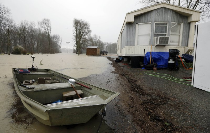 As backflow waters flood home property and farm land along Mississippi 16 near Rolling Fork, Miss., some residents have taken to using small boats to reach their homes, Monday, March 11, 2019. (FEMA), the Mississippi Emergency Management Agency (MEMA), along with select local emergency management offices will be conducting joint damage assessments in response to the severe storms and flooding are impacting the state. (AP Photo/Rogelio V. Solis)