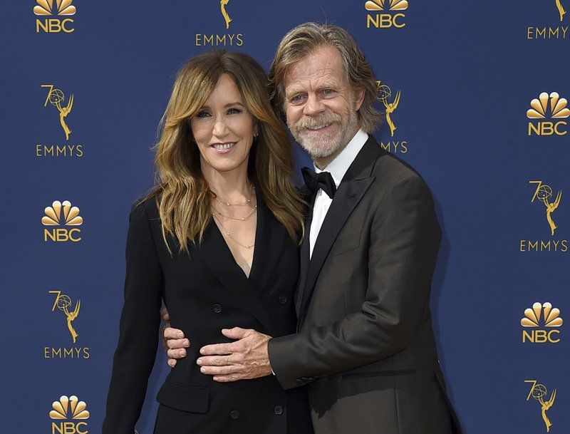 FILE - In this Sept. 17, 2018 file photo, Felicity Huffman, left, and William H. Macy arrive at the 70th Primetime Emmy Awards in Los Angeles. (Photo by Jordan Strauss/Invision/AP, File)