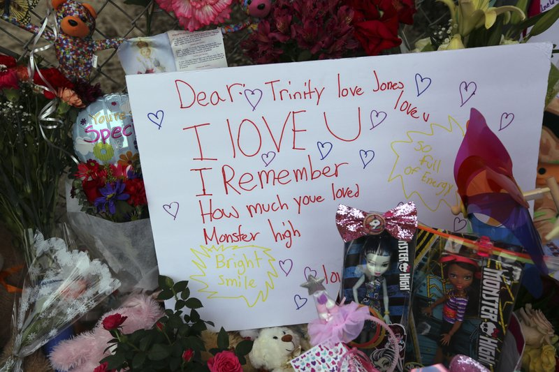 Dozens of tributes are seen at a large memorial to Trinity Love Jones, the 9-year-old girl whose body was found in a duffel bag along a suburban Los Angeles equestrian trail, seen at rear, in Hacienda Heights, Calif. (AP Photo/Reed Saxon)