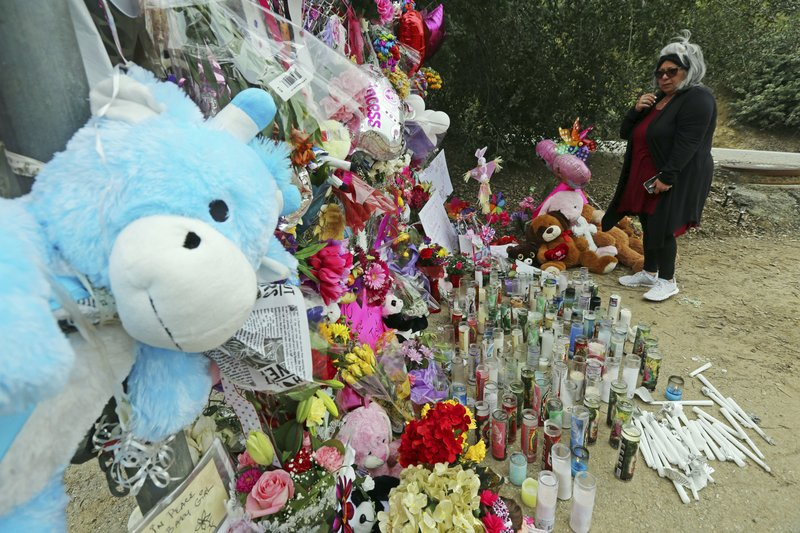 A woman crosses herself at a large memorial to Trinity Love Jones, the 9-year-old girl whose body was found in a duffel bag along a suburban Los Angeles equestrian trail in Hacienda Heights, Calif. (AP Photo/Reed Saxon)