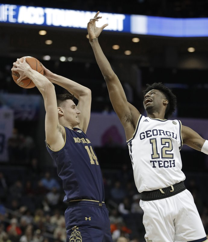 Notre Dame's Nate Laszewski (14) grabs a rebound in front of Georgia Tech's Khalid Moore (12) during the first half of an NCAA college basketball game in the Atlantic Coast Conference tournament in Charlotte, N. (AP Photo/Nell Redmond)