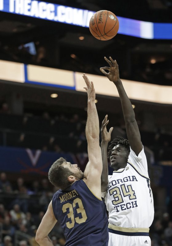 Georgia Tech's Abdoulaye Gueye (34) shoots over Notre Dame's John Mooney (33) during the first half of an NCAA college basketball game in the Atlantic Coast Conference tournament in Charlotte, N. (AP Photo/Nell Redmond)