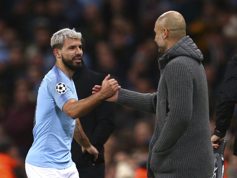 Manchester City coach Pep Guardiola, right, shakes hands with Manchester City's Sergio Aguero during the Champions League round of 16 second leg, soccer match between Manchester City and Schalke 04 at Etihad stadium in Manchester, England, Tuesday, March 12, 2019. (AP Photo/Dave Thompson)