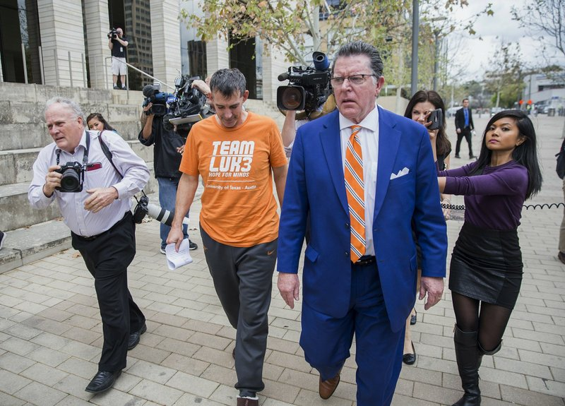Texas men's tennis coach Michael Center, center left, walks with Defense lawyer Dan Cogdell, center right, away from the United States Federal Courthouse in Austin, Texas, Tuesday, March 12, 2019. (Ricardo B. Brazziell
