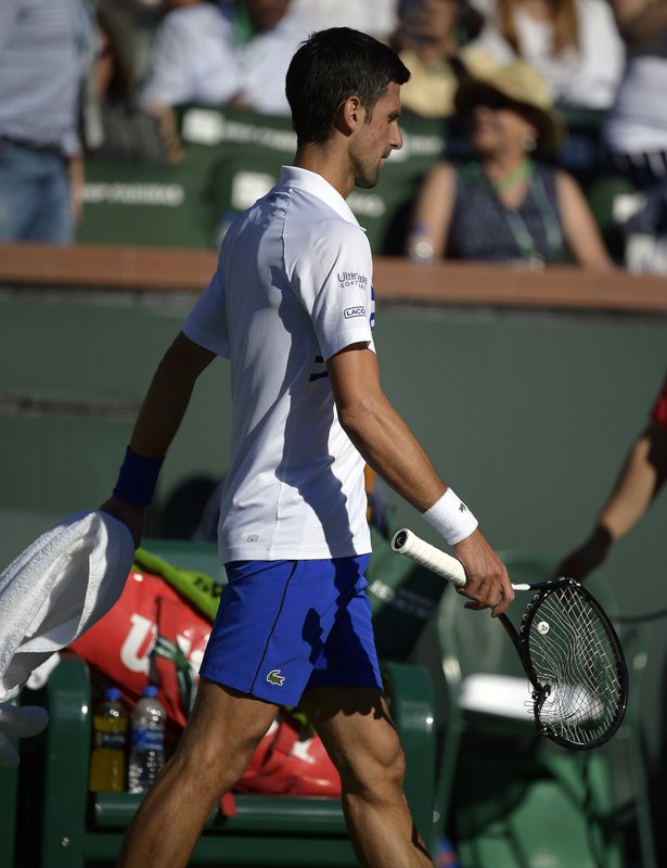 Novak Djokovic, of Serbia, holds his racket which he broke in anger after losing the first set to Philipp Kohlschreiber, of Germany, at the BNP Paribas Open tennis tournament Tuesday, March 12, 2019 in Indian Wells, Calif. (AP Photo/Mark J. Terrill)