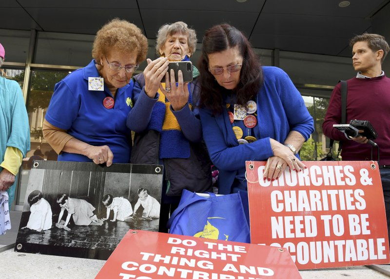 Protesters gather outside the County Court during the sentencing of Cardinal George Pell in Melbourne, Australia, Wednesday, March. (AP Photo/Andy Brownbill)