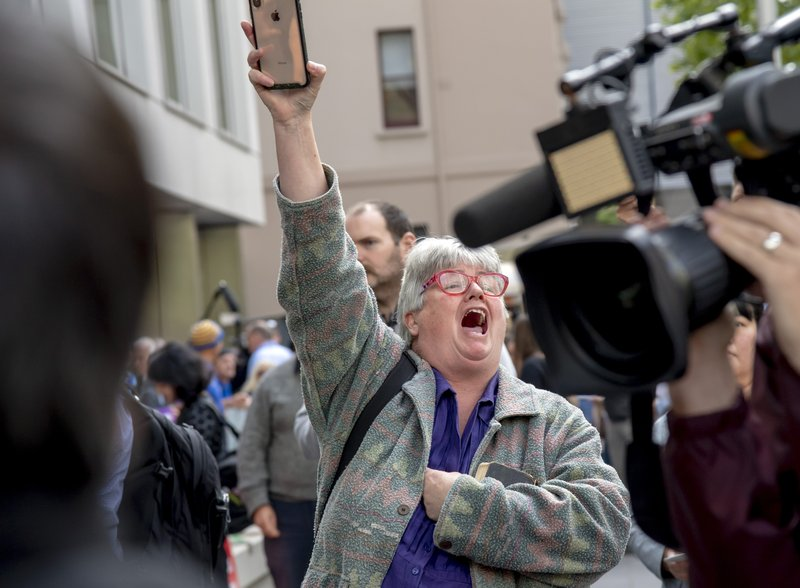 A woman reacts outside the County Court after the sentencing of Cardinal George Pell in Melbourne, Australia, Wednesday, March 13, 2019. (AP Photo/Andy Brownbill)