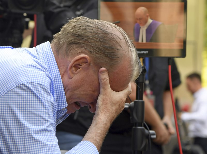 A man reacts outside the County Court during the sentencing of Cardinal George Pell in Melbourne, Australia, Wednesday, March 13, 2019. (AP Photo/Andy Brownbill)