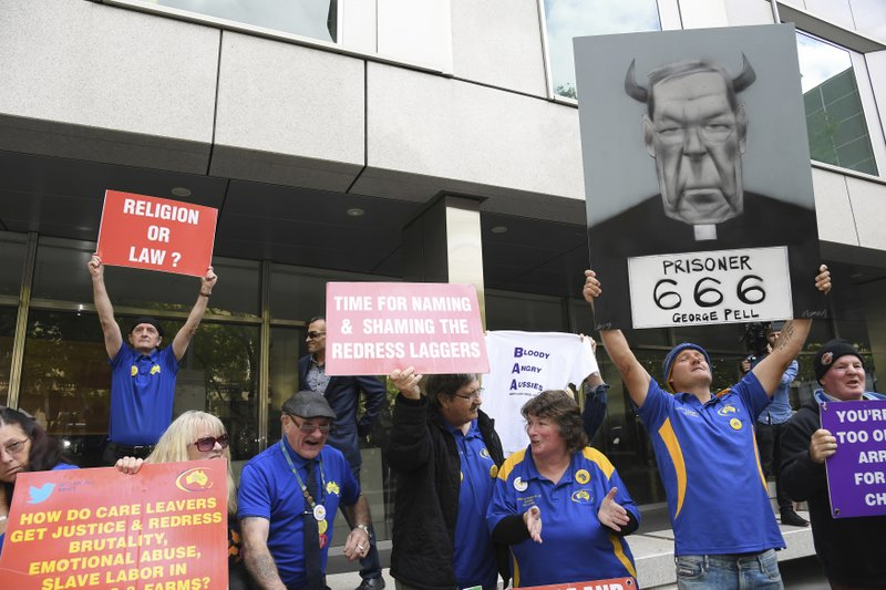 Protesters gather outside the County Court during the sentencing of Cardinal George Pell in Melbourne, Australia, Wednesday, March 13, 2019. (AP Photo/Andy Brownbill)