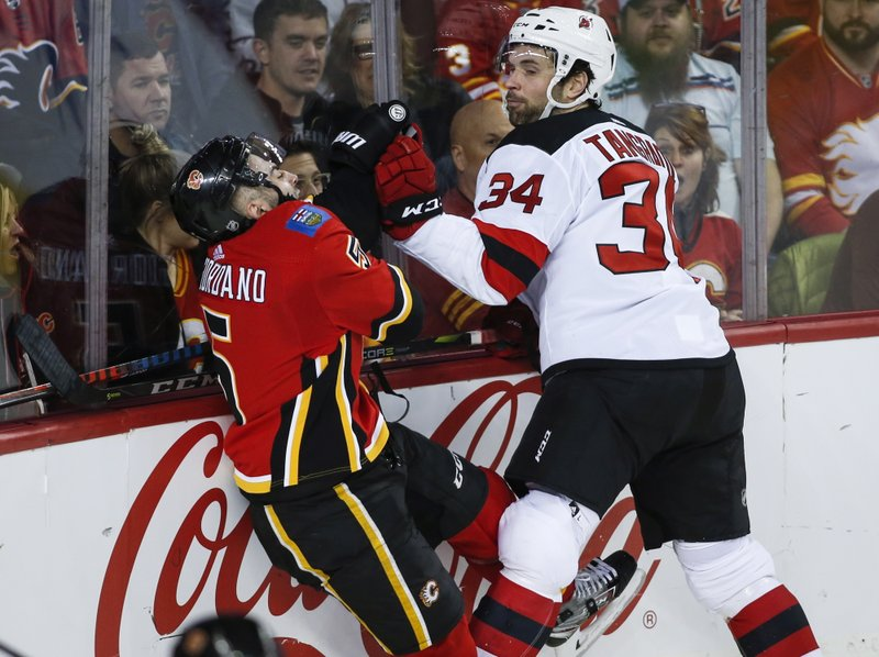 New Jersey Devils' Eric Tangradi, right, checks Calgary Flames' Mark Giordano during the second period of an NHL hockey game Tuesday, March 12, 2019, in Calgary, Alberta. (Jeff McIntosh/The Canadian Press via AP)