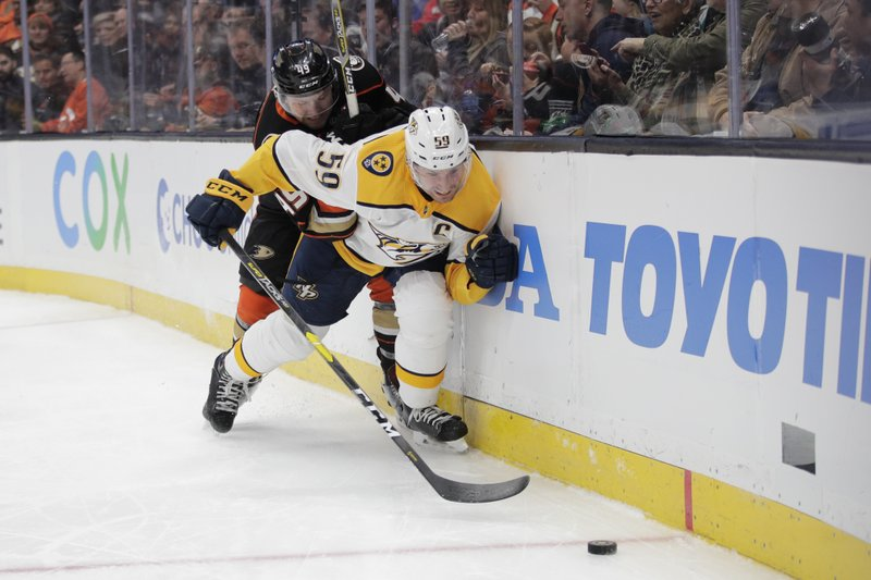Nashville Predators' Roman Josi, front, of Switzerland, is shoved by Anaheim Ducks' Max Jones while chasing the puck during the second period of an NHL hockey game, Tuesday, March 12, 2019, in Anaheim, Calif. (AP Photo/Jae C. Hong)