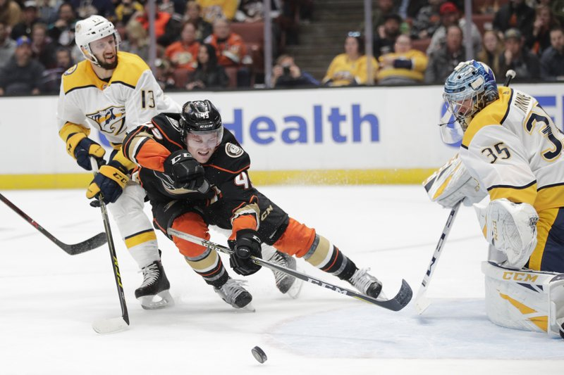 Anaheim Ducks' Max Jones, center, loses his balance in front of Nashville Predators goaltender Pekka Rinne, right, of Finland, after he was pushed by Predators' Nick Bonino during the second period of an NHL hockey game, Tuesday, March 12, 2019, in Anaheim, Calif. (AP Photo/Jae C. Hong)