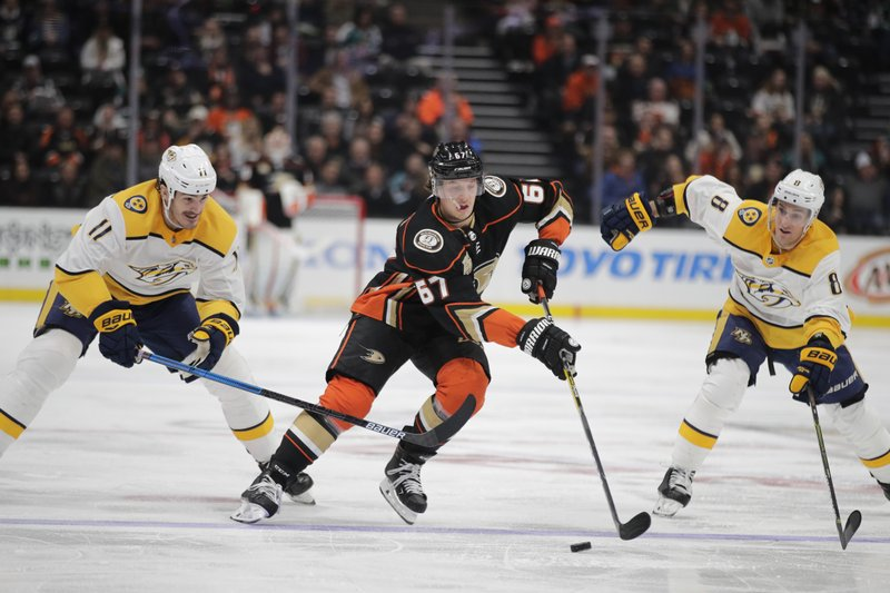 Anaheim Ducks' Rickard Rakell, center, of Sweden, moves the puck past Nashville Predators' Brian Boyle, left, and Kyle Turris during the second period of an NHL hockey game, Tuesday, March 12, 2019, in Anaheim, Calif. (AP Photo/Jae C. Hong)