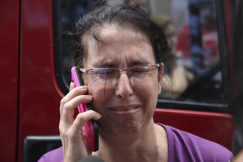 A woman uses her cell phone as she waits for news outside the Raul Brasil State School in Suzano, Sao Paulo state, Brazil, Wednesday, March 13, 2019. (Mauricio Sumiya/Futura Press via AP)