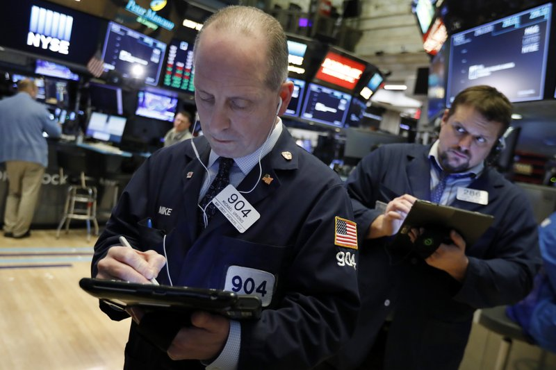 Trader Michael Urkonis, left, works on the floor of the New York Stock Exchange, Wednesday, March 13, 2019. (AP Photo/Richard Drew)