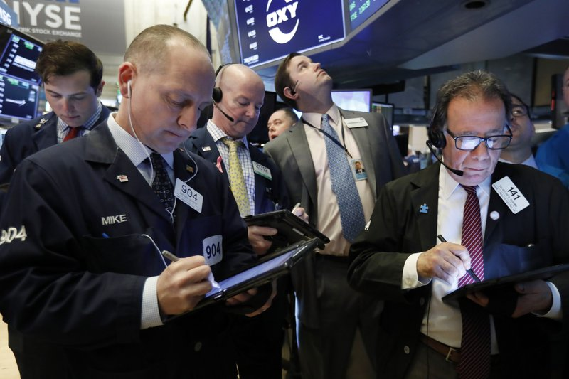 Traders gather at the post that handles Oaktree Capital Group on the floor of the New York Stock Exchange, Wednesday, March 13, 2019. (AP Photo/Richard Drew)