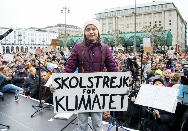 Swedish climate activist Greta Thunberg holds a protest poster as she attends a protest rally in Hamburg, Germany, Friday, March 1, 2019. (Daniel Reinhardt/dpa via AP)