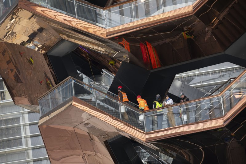In this March 8, 2019 photo, workers climb the stairs of the