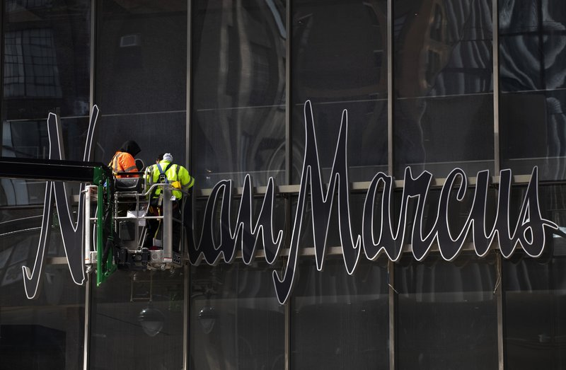 In this March 8, 2019 photo, workers install a sign for the Neiman Marcus department store at the Hudson Yards development in New York. (AP Photo/Mark Lennihan)