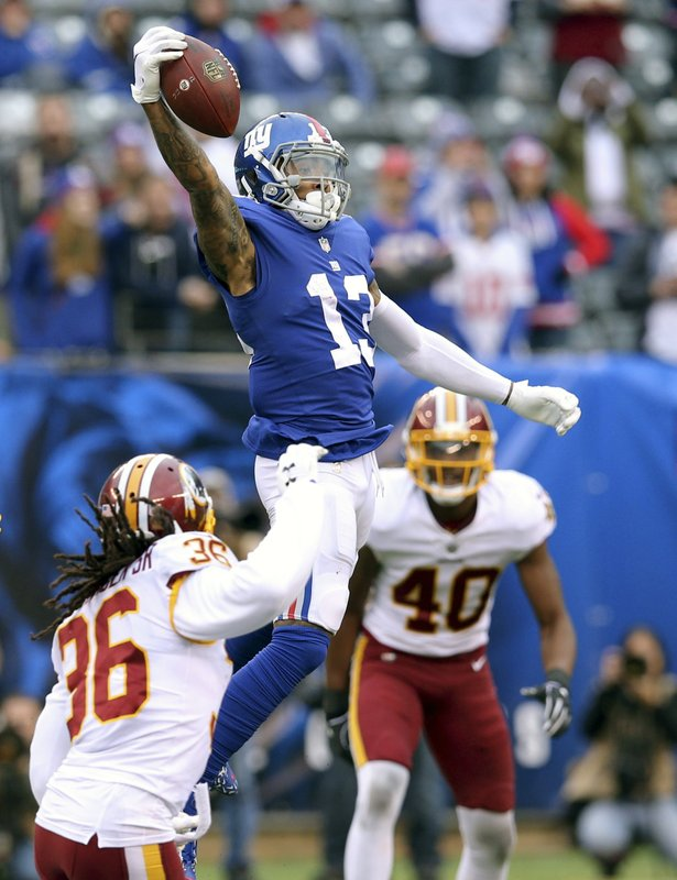 FILE - In this Oct. 28, 2018, file photo, New York Giants wide receiver Odell Beckham Jr. (13) makes a one handed catch against Washington Redskins safety D. (36) and linebacker Josh Harvey-Clemons (40) during an NFL football game, in East Rutherford, N.J. No longer a punching bag, the Browns are punching back. From hopeless to hopeful. Finally.  In landing Beckham, one of the game's most electrifying players, the Browns have risen from the deepest depths imaginable in just a year. (AP Photo/Brad Penner, File)
