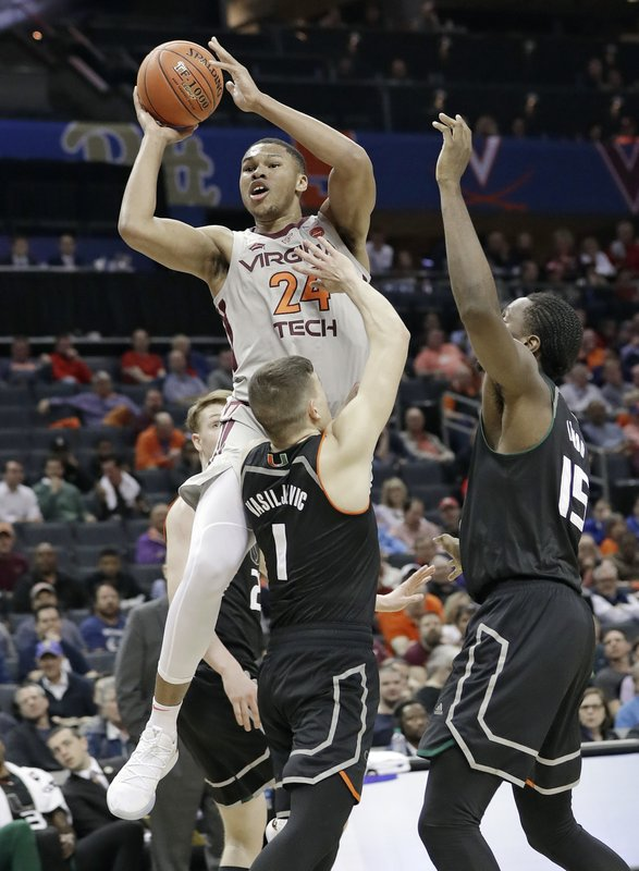 Virginia Tech's Kerry Blackshear Jr. (24) shoots against Miami's Dejan Vasiljevic (1) and Ebuka Izundu (15) during the first half of an NCAA college basketball game in the Atlantic Coast Conference tournament in Charlotte, N. (AP Photo/Chuck Burton)