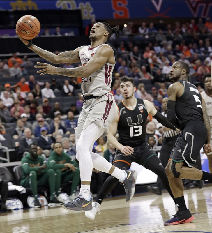 Virginia Tech's Ahmed Hill, left, drives past Miami's Anthony Mack (13) and Zach Johnson (5) during the first half of an NCAA college basketball game in the Atlantic Coast Conference tournament in Charlotte, N. (AP Photo/Chuck Burton)