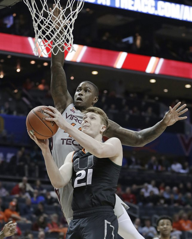 Miami's Sam Waardenburg (21) drives against Virginia Tech's Ty Outlaw (42) during the first half of an NCAA college basketball game in the Atlantic Coast Conference tournament in Charlotte, N. (AP Photo/Nell Redmond)