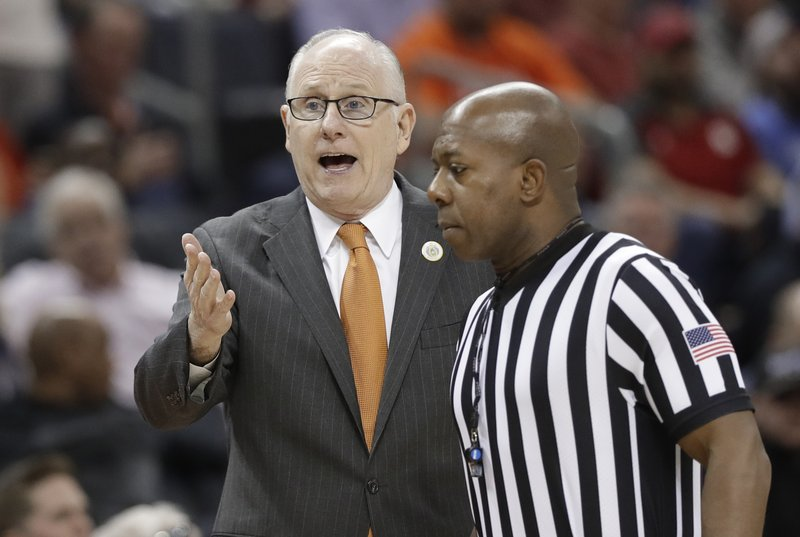 Miami head coach Jim Larranaga, left, talks to an official during the first half of an NCAA college basketball game against Virginia Tech in the Atlantic Coast Conference tournament in Charlotte, N. (AP Photo/Chuck Burton)