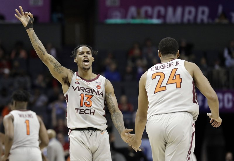Virginia Tech's Ahmed Hill (13) reacts as he congratulates Kerry Blackshear Jr. (24) after a basket against Miami during the first half of an NCAA college basketball game in the Atlantic Coast Conference tournament in Charlotte, N. (AP Photo/Chuck Burton)