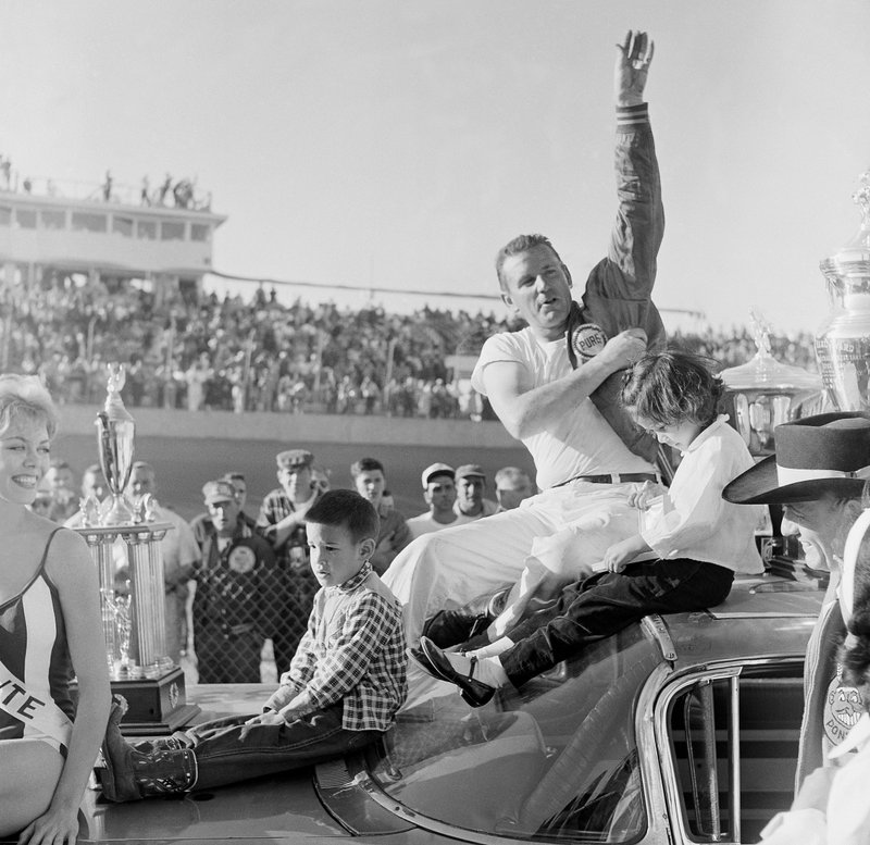 FILE - In this Feb. 26, 1961, file photo, Marvin Panch, Daytona Beach winner of the 500-mile late model stock car race, waves to the crowd as he sits on top of his car with his two kids, Marvin, left, and Lynn, in Daytona Beach Fla. (AP Photo/File)