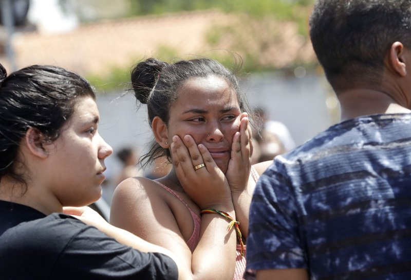 A student cries outside the Raul Brasil State School in Suzano, the greater Sao Paulo area, Brazil, Wednesday, March 13, 2019. (AP Photo/Andre Penner)