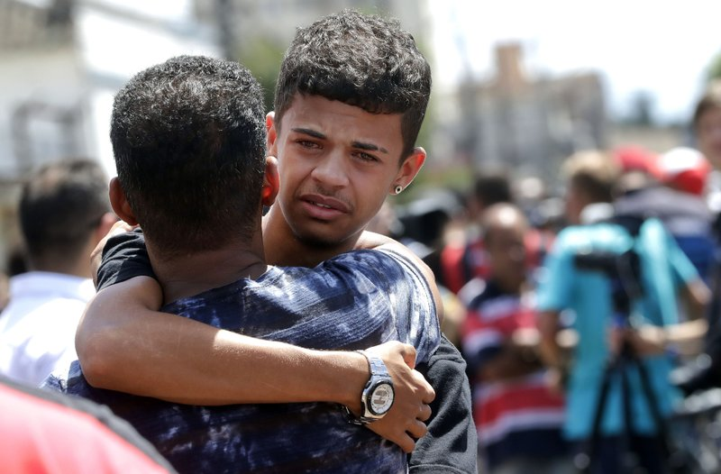 A former student is comforted by a friend outside the Raul Brasil State School in Suzano, the greater Sao Paulo area, Brazil, Wednesday, March 13, 2019. (AP Photo/Andre Penner)
