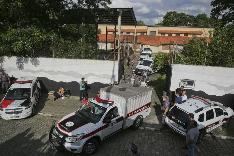 Forensic vehicles transport the bodies of the people who were killed in a school shooting at the Raul Brasil State School in Suzano, in the greater Sao Paulo area, Brazil, Wednesday, March 13, 2019. (AP Photo/Andre Penner)