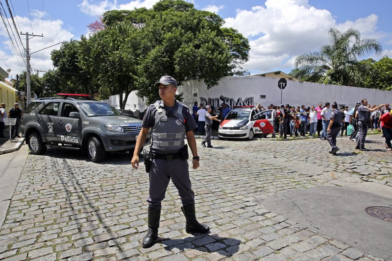Police officers stand guard outside the Raul Brasil State School in Suzano, the greater Sao Paulo area, Brazil, Wednesday, March 13, 2019. (AP Photo/Andre Penner)