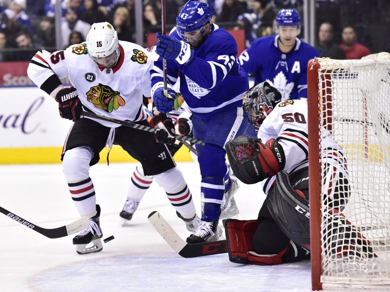 Chicago Blackhawks center Artem Anisimov (15) and Toronto Maple Leafs center Nazem Kadri (43) battle in front of Blackhawks goaltender Corey Crawford (50) during the first period of an NHL hockey game Wednesday, March 13, 2019, in Toronto. (Frank Gunn/The Canadian Press via AP)
