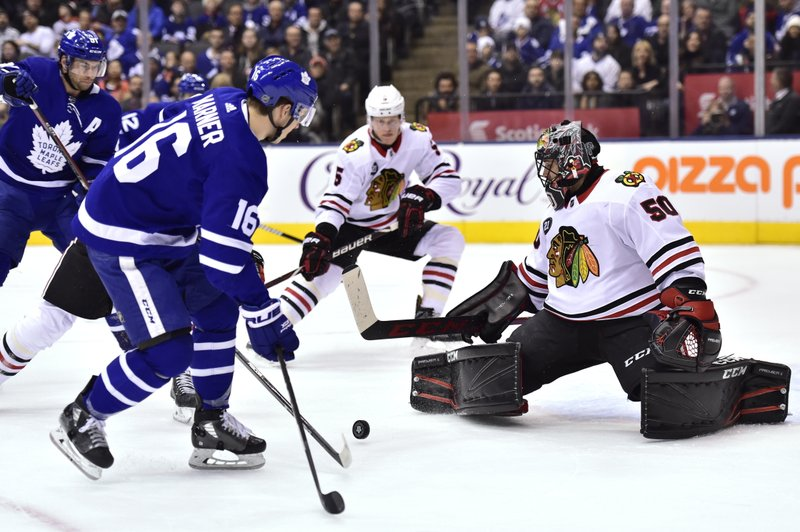 Toronto Maple Leafs right wing Mitchell Marner (16) looks to control a pass as Chicago Blackhawks goaltender Corey Crawford (50) watches during the first period of an NHL hockey game Wednesday, March 13, 2019, in Toronto. (Frank Gunn/The Canadian Press via AP)