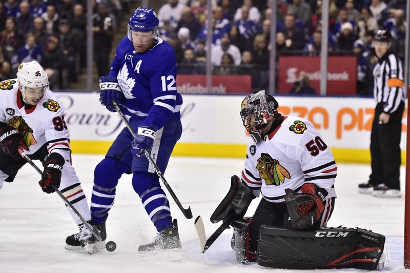 Chicago Blackhawks goaltender Corey Crawford (50) keeps his eye on the puck as right wing Dylan Sikura (95) and Toronto Maple Leafs center Patrick Marleau (12) work in front of him during the first period of an NHL hockey game Wednesday, March 13, 2019, in Toronto. (Frank Gunn/The Canadian Press via AP)