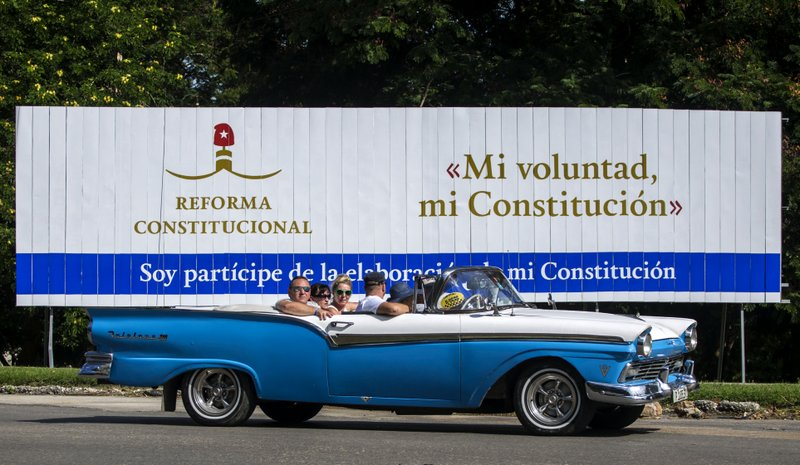 FILE - In this Oct. 2, 2018 file photo, tourists take a joy ride in a vintage convertible car, past a billboard promoting constitutional reform with the Spanish messages: