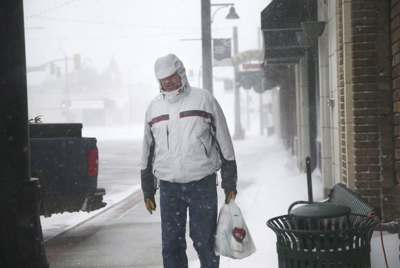 A man walks along 17th Street during a blizzard on Wednesday, March 13, 2019, in Cheyenne. White-out conditions closed I-80, I-25, and U. (Jacob Byk/The Wyoming Tribune Eagle via AP)