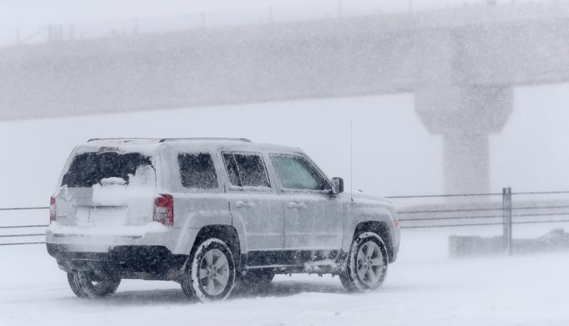A Jeep Compass sits in one of the eastbound lanes of Interstate 70 near Tower Road as a late winter storm packing hurricane-force winds and snow sweeps over the intermountain West and stops traffic Wednesday, March 13, 2019, in Aurora, Colo. (AP Photo/David Zalubowski)