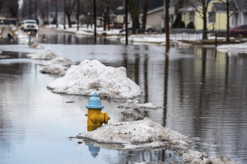 Water rises on Avenue I at North 26th Street Wednesday, March 13, 2019, in Council Bluffs, Iowa. Flooding forced evacuations in northeast Nebraska and western Iowa, including a retirement home in Pierce, Neb. (Chris Machian/Omaha World-Herald via AP)