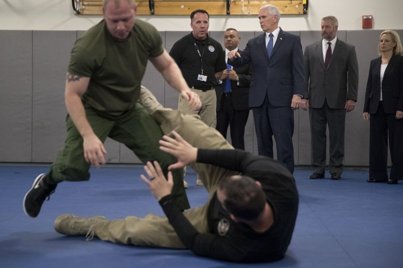 Vice President Mike Pence, third from right, watches non-lethal hand to hand combat training while visiting the U. (AP Photo/Andrew Harnik)