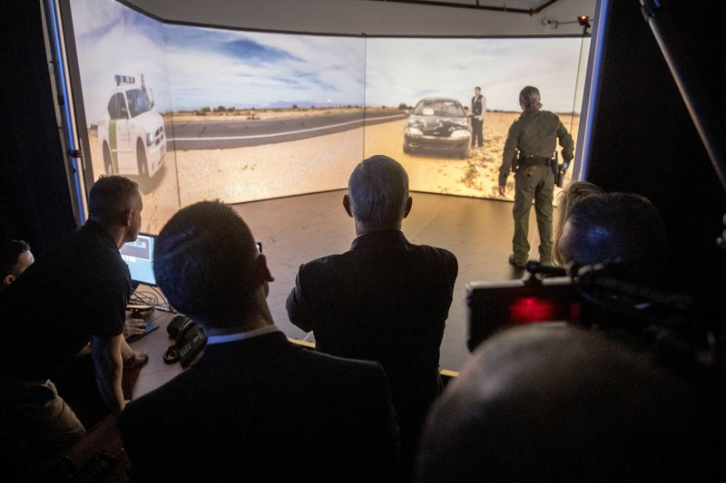 Vice President Mike Pence, center, is shown a Virtual Simulator Training exercise by facility assistant director Peter Lobur, left, and Border Patrol Agent Christina Wroldson, right, during a visit to the U. (AP Photo/Andrew Harnik)