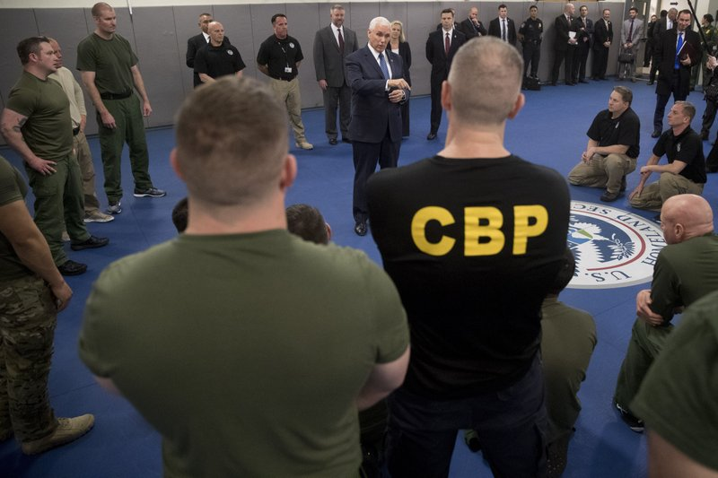 Vice President Mike Pence speaks to agents and agents-in-training as he visits a non-lethal hand to hand combat training class while visiting the U. (AP Photo/Andrew Harnik)