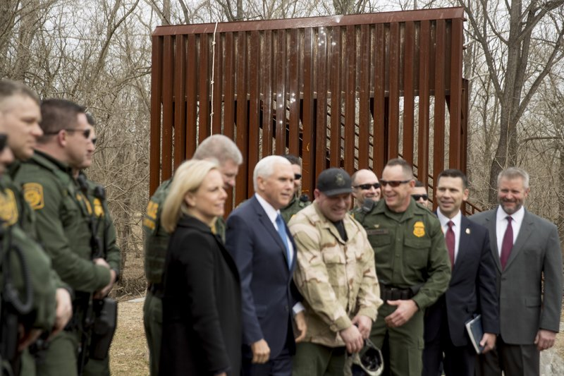 A section of a border wall used for training is visible behind Vice President Mike Pence, center, as he poses for a photograph with Border Patrol agents following a border wall training demonstration at the U. (AP Photo/Andrew Harnik)