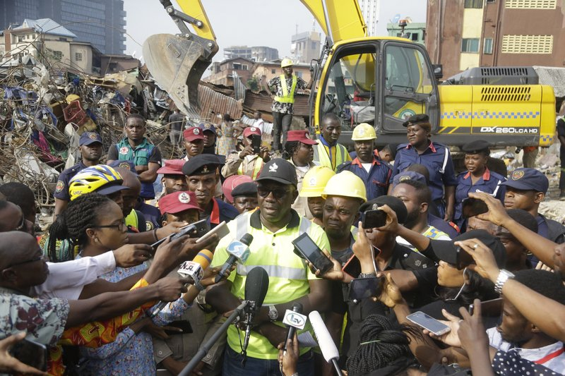 General Manager of Lagos State Emergency Management Agency Tiamiyu Adesina, center, updates the press at the scene of a collapsed building in Lagos, Nigeria, Thursday March 14, 2019. (AP Photo/Sunday Alamba)