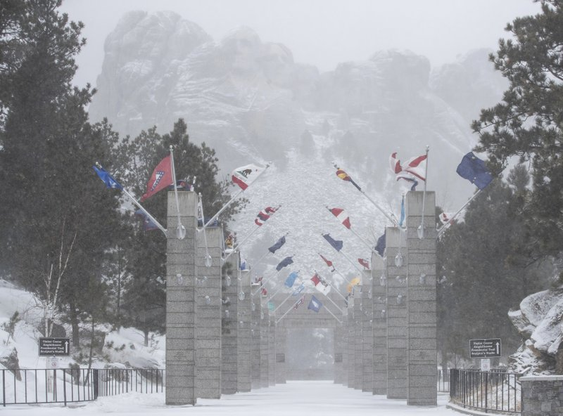 Blowing snow reduces visibility at the Mount Rushmore National Memorial near Keystone, S.D., Wednesday, March 13, 2019. (Ryan Hermens/Rapid City Journal via AP)