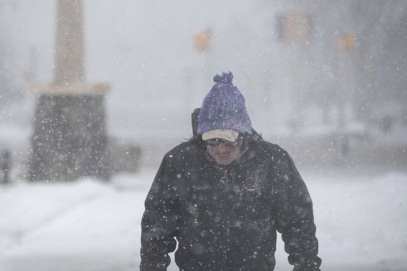 Francis Rotenberger, of Rapid City, S.D., walks home through Memorial Park in the snow in downtown Rapid City Wednesday, March 13, 2019. (Ryan Hermens/Rapid City Journal via AP)